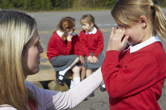 Teacher Comforting Victim Of Bullying In Playground Stock Photography