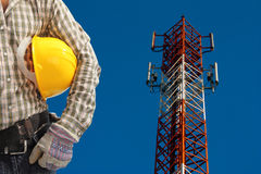 Technician against telecommunication tower, painted white and re Royalty Free Stock Image