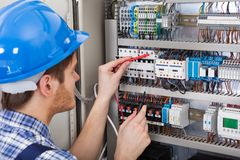 Technician examining fusebox with multimeter probe Stock Images