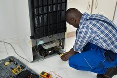 Technician Fixing Refrigerator With Worktool Stock Image