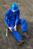 Technician suffering from knee pain on street Royalty Free Stock Image