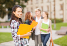 Teenage girl with folders and mates on the back Stock Image