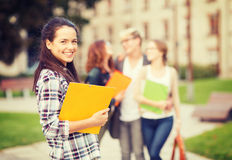 Teenage girl with folders and mates on the back Royalty Free Stock Photo