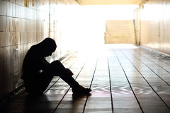 Teenager depressed sitting inside a dirty tunnel Stock Images
