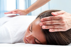Therapists hands doing reiki therapy on girl. Stock Photography