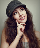 Thinking teen girl in fashion cap looking up Stock Image