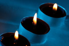Three blue candles are glowing in the darkness Stock Photography