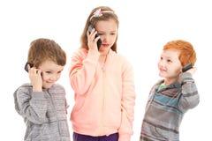 Three children talking on kids mobile phone Stock Image