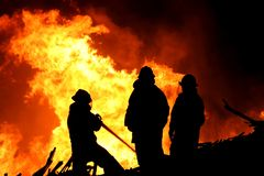 Three fire fighters and flames Stock Photos