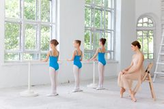 Three little ballerinas dancing with personal ballet teacher in dance studio Royalty Free Stock Images