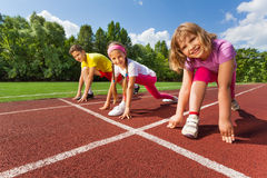 Three smiling children in ready position to run Stock Photo