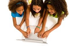 Three young girls on laptopThree multi-ethnic pre adolescent girls sharing a computer, isolated on white background Royalty Free Stock Images
