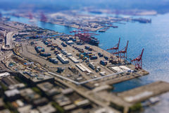 Tilt shift of shipping port with containers and loading transport ship with cargo Royalty Free Stock Images