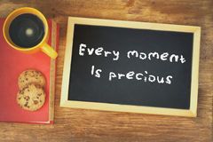 Top view of blackboard with the phrase every moment is precious next to coffee cup over wooden table Stock Images
