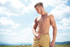 Topless man outdoor with hand on pants looks down Stock Photo