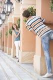 Tourist couple playing hide-and-seek amongst columns Stock Photo