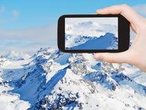 Tourist taking photo of snow mountains in Alpes Royalty Free Stock Photography