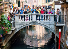 Tourists making photos on a bridge over channel in Venice, Italy Stock Image