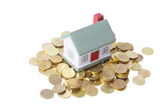 Toy small house standing on a heap of coins. Stock Image