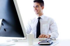 Trabajo joven feliz del hombre de negocios en oficina moderna en el ordenador Foto de archivo libre de regalías
