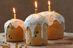 Traditional ukrainian culture easter cake called kulich sweet bread with three burning candles and icing on rustic textile Stock Images