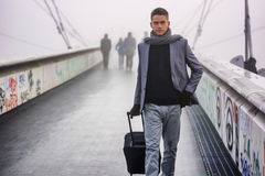 Trendy handsome man walking with a suitcase Stock Image