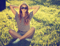 Trendy Hipster Girl Relaxing on the Grass Stock Images
