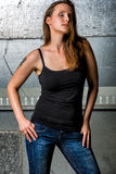 Trendy Woman in blue jeans posing in the grungy underground Stock Photo