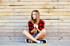 Trendy young girl posing against wooden wall background. Modern Stock Photos