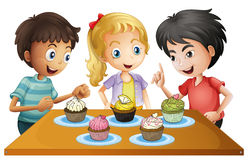 Trois enfants à la table avec des petits gâteaux Photo libre de droits