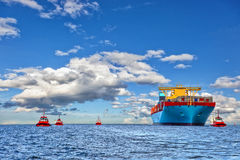 Tugboats and container ship Stock Image