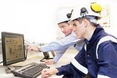 Två teknikerer som tillsammans diskuterar arbete i regeringsställning Royaltyfria Bilder