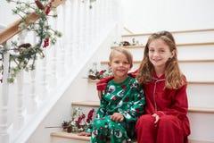 Twee Kinderen die op Treden in Pyjama's bij Kerstmis zitten Stock Foto