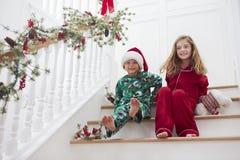 Twee Kinderen die op Treden in Pyjama's bij Kerstmis zitten Stock Fotografie