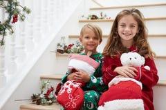 Twee Kinderen die op Treden in Pyjama's bij Kerstmis zitten Royalty-vrije Stock Afbeelding