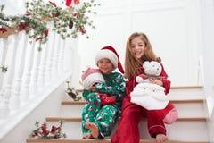 Twee Kinderen die op Treden in Pyjama's bij Kerstmis zitten Royalty-vrije Stock Foto's
