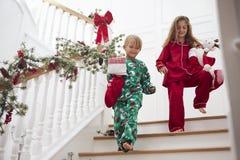 Twee Kinderen op Treden in Pyjama's met Kerstmiskousen Stock Afbeeldingen
