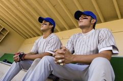 Two baseball team-mates sitting in dugout Stock Image