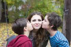 Two boys kissing a teenage girl Stock Images