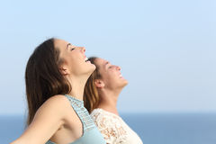 Two girls breathing deep fresh air on the beach Stock Images