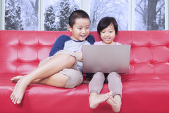 Two kids using laptop on sofa Royalty Free Stock Photography
