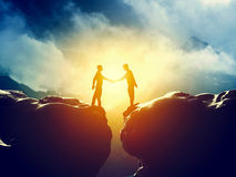 Two men handshake over mountains precipice. Business Royalty Free Stock Photo