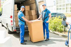 Two Movers Loading Boxes In Truck Royalty Free Stock Image