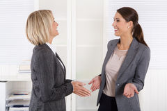 Two successful happy businesswoman talking together. Royalty Free Stock Photos