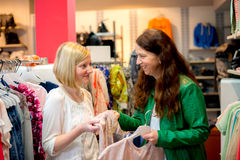 Two woman in the clothes shop Stock Photos