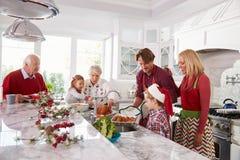 Uitgebreide Familiegroep die Kerstmismaaltijd in Keuken voorbereiden Stock Foto's