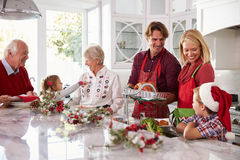 Uitgebreide Familiegroep die Kerstmismaaltijd in Keuken voorbereiden Stock Afbeelding
