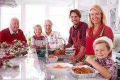 Uitgebreide Familiegroep het Bedruipen Kerstmis Turkije in Keuken Royalty-vrije Stock Foto's