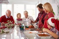 Uitgebreide Familiegroep het Bedruipen Kerstmis Turkije in Keuken Royalty-vrije Stock Foto