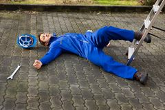 Unconscious technician fell from ladder on street Royalty Free Stock Images